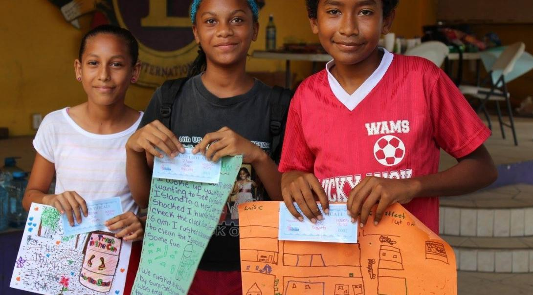 A Projects Abroad volunteer working with children in Belize helps children celebrate with certificates they recieved for their hard work at a summer camp.